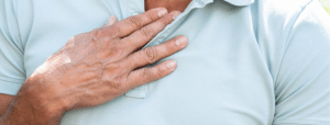 person holding their chest from heartburn symptoms