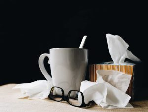 tissues and teacup with straw on bedside table when you're unable to stay well during winter
